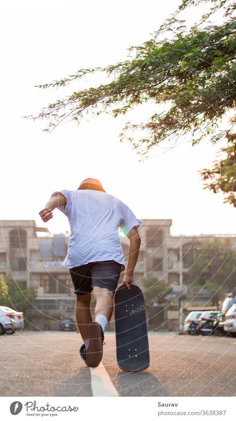 Ein junger Erwachsener stürmt bei Sonnenaufgang mit seinem Skateboard auf einer leeren Straße vor. Sommer Skateboarding Erholung covid-19 leere Straße