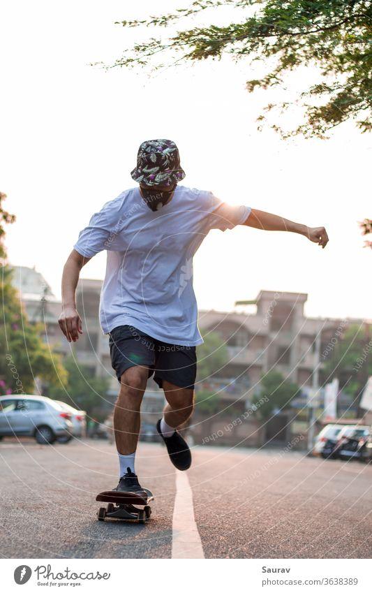 Frontansicht eines jungen Erwachsenen, der auf einer leeren Straße Skateboard fährt, während er bei Sonnenaufgang eine Schutzmaske trägt. Sommer Mundschutz