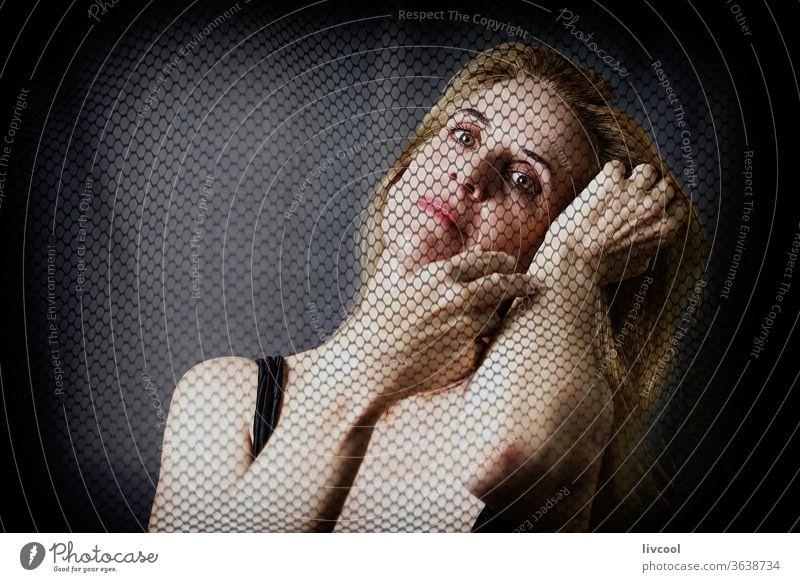 schöne reife Frau durch einen Tüll Porträt Erwachsener Schönheit gestikulierend romantische Haltung Gesicht Hände Vor dunklem Hintergrund Finger Tüfteln
