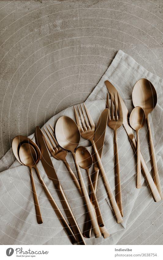 Goldene Besteckkomposition auf grauem Hintergrund - Löffel, Gabel und Messer gold Silberwaren Utensilien Küchengeräte vereinzelt Essen zubereiten Lebensmittel