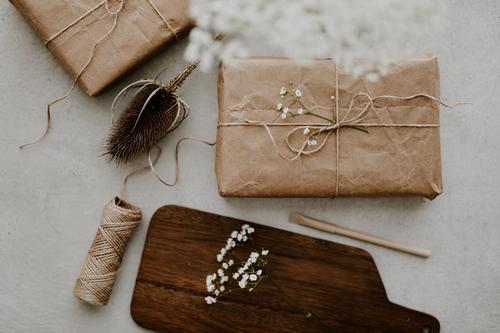 Geschenk verpackt in umweltfreundlichem Recyclingpapier mit Trockenblumen und Schnur umhüllen diy Hintergrund beige Überraschung Weihnachten Geburtstag Kasten