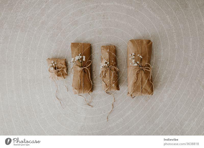 Vier in Papier verpackte Geschenke mit getrockneten Blumen und Schnur auf Marmorgrund Paket Verpackung Feiertag Überraschung wiederverwendbar