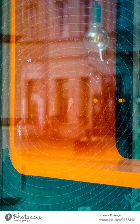 Schaufenster mit einem farbenfrohen Element, einer alten Glühbirne und einer Spiegelung des Gebäudes dekorativ Farbbild im Freien abstrakter Hintergrund