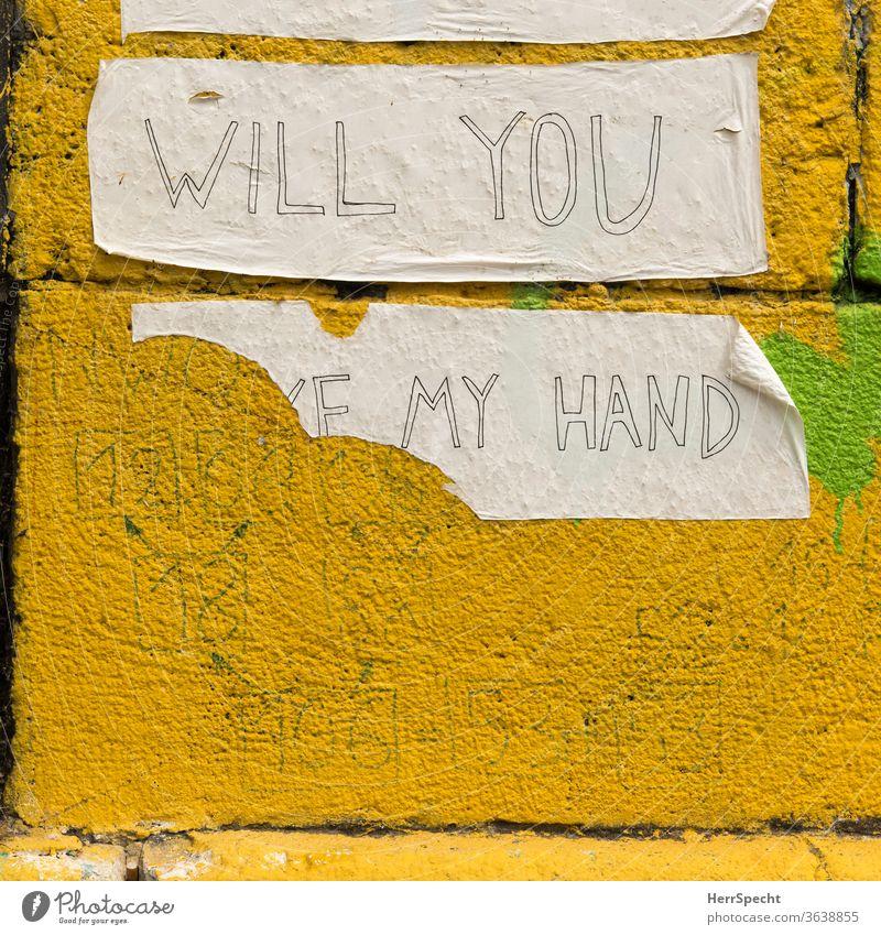 Will you take my hand? Graffiti klebestreifen Händchenhalten Hand Fragen abgerissen aufgeklebt Botschaft Wand Mauer Schriftzeichen gelb unvollständig