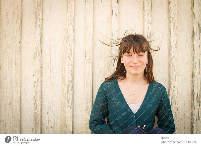 Jugendliche steht mit geschlossenen Augen vor einer hellen Holzwand und genießt den Wind in den Haaren. teenager Meditation mediterran mediteran Mädchen