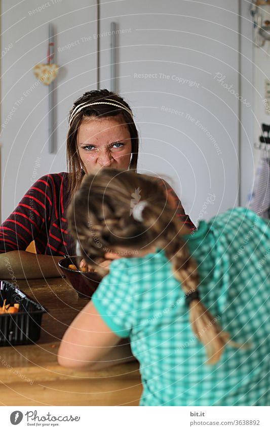 Zwei Teenager sitzen zuhause in der Küche am Tisch und schneiden Gemüse und Grimasse. Lustige Schwestern helfen daheim bei Hausarbeit, machen Quatsch und haben Spaß. Weibliche Geschwister von vorne und hinten, mit hübschen Frisuren. Pädagogisch wertvoll.