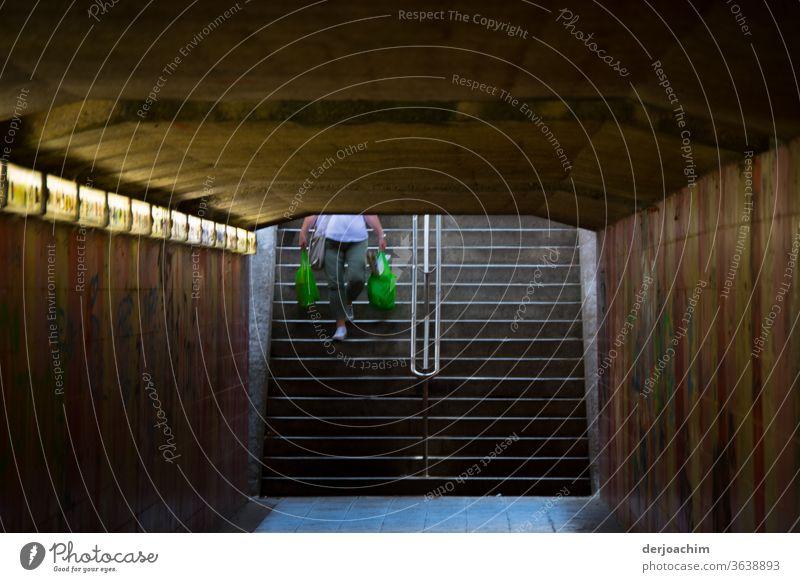 Eine Ältere Frau schleppt zwei große grüne Taschen mit ihrem Einkauf. Sie geht damit die Treppe hinunter. Sie betritt gleich die Unterführung, zurStadt. Tunnel