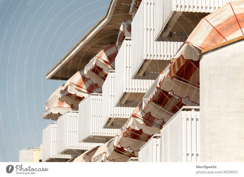 Balkone mit bunten Markisen Streifen Urlaubsstimmung zuhause bleiben stay at home Pandemie Daheim bleiben Haus Mehrfamilienhaus nebeneinander NAchbarschaft