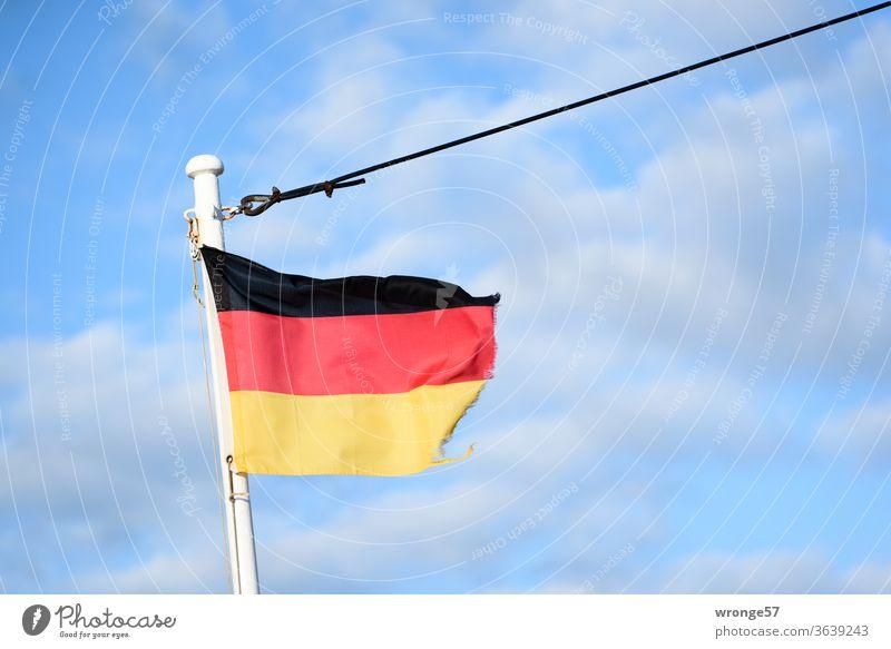 Ausgefranste deutsche Flagge flattert im Wind am Mast eines Schiffes unter blauem Himmel Fahne Deutschland Deutsche Flagge Bugmast Fahnenmast schwarzrotgold