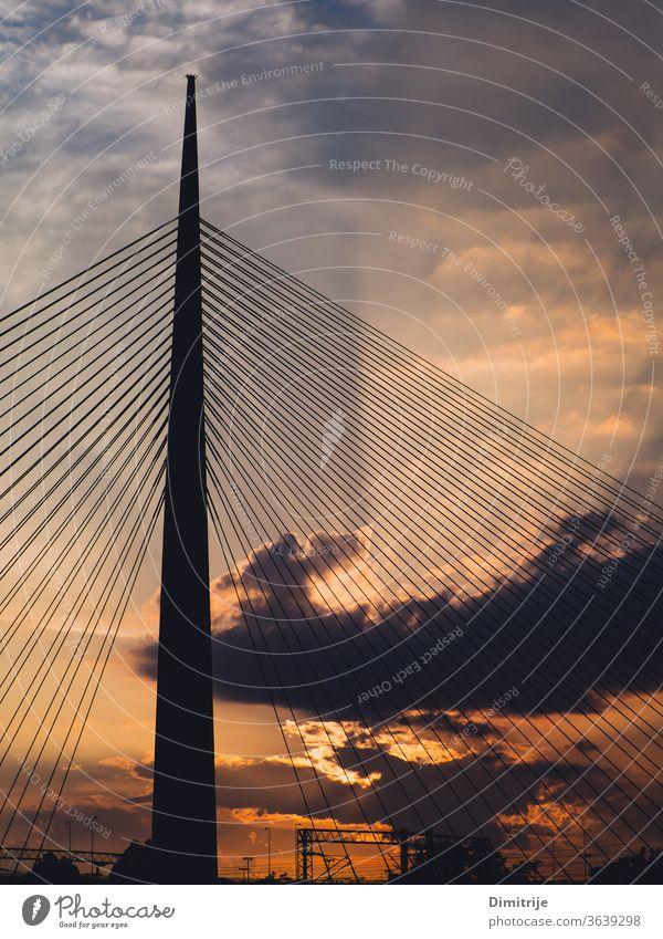 Großer Hängebrückenturm bei Sonnenuntergang - Sonnenstrahlen durch die Wolken im Hintergrund Brücke modern Suspension Architektur Himmel Wasser Stahl Großstadt
