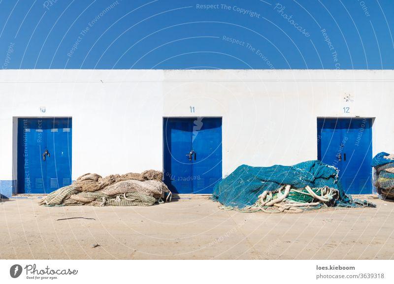 Hafenlagergebäude mit blauen Türen und Fischernetzen, Altea, Costa Blanca, Spanien Netz MEER Portwein Natur Wasser Fischereiindustrie hafen reisen Fischen