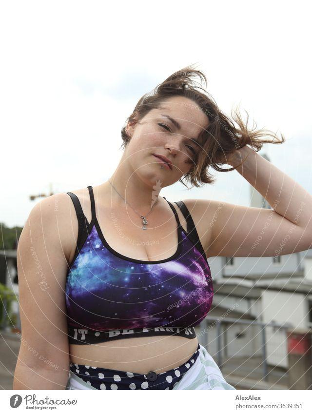 Portrait einer jungen Frau mit bauchfreien Top die sich durch die Haare fährt junge Frau windig brünett schön intensiv Jugendliche 18-25 Jahre Stadtlandschaft