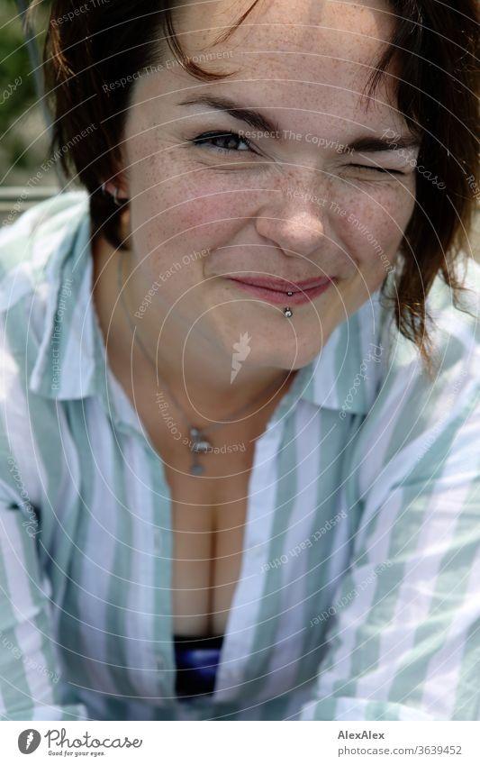 Portrait einer jungen, sommersprossigen Frau zwinkert und lächelt junge Frau Top windig Haare brünett schön intensiv Jugendliche 18-25 Jahre Dekolleté