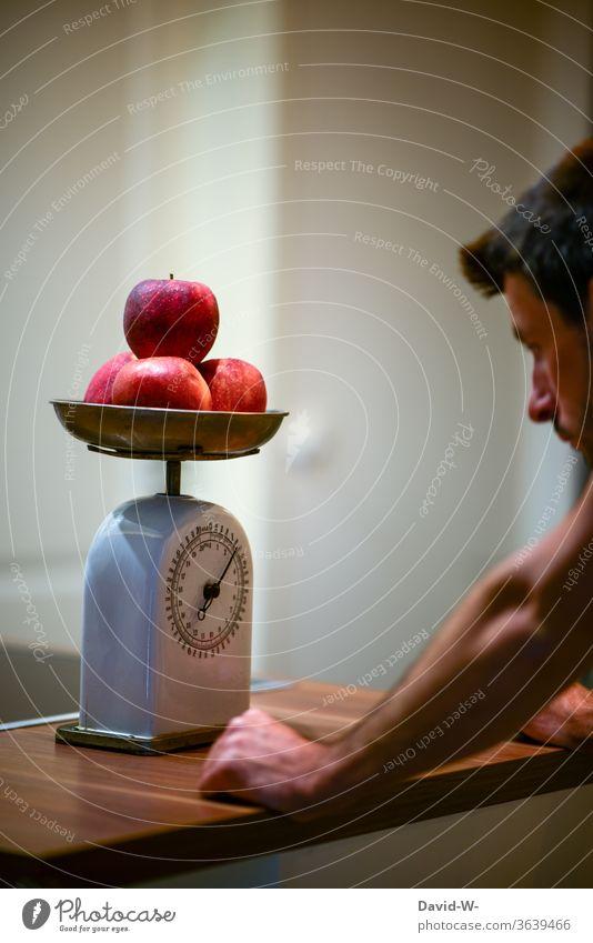 Mann ermittelt mit einer alten Küchenwaage das Gewicht von ein paar Äpfeln Waage ermitteln ablesen Zahlen Kg pfund anzeige genau genauigkeit Obst vorbereitung
