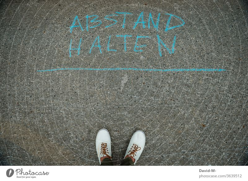 Abstand halten - Person steht auf der Straße und hält Abstand Corona geschrieben wörter Satz coronavirus Coronavirus Corona-Virus Pandemie Infektionsgefahr