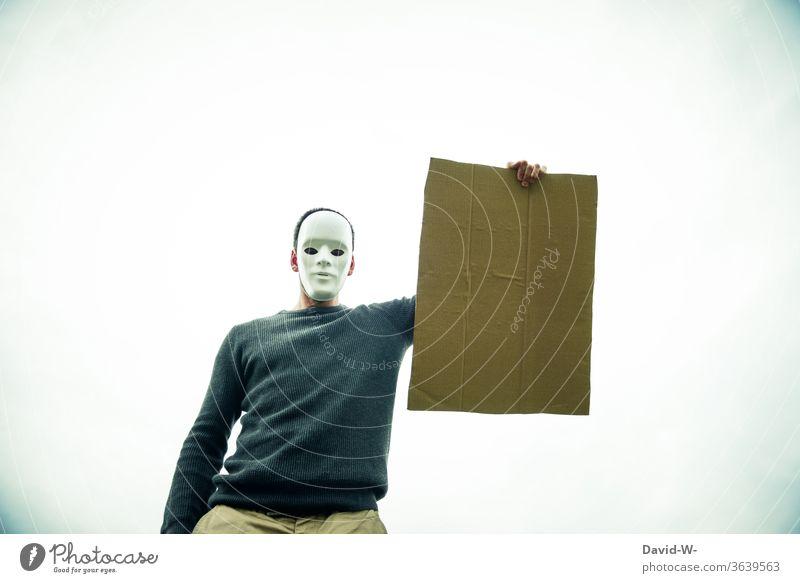 anonym - maskierter Mann hält ein leeres Schild aus Pappkarton in die Luft Karton Pappe anonymous Maske Anonymität pappkarton Hinweis hinweisend Sicherheit