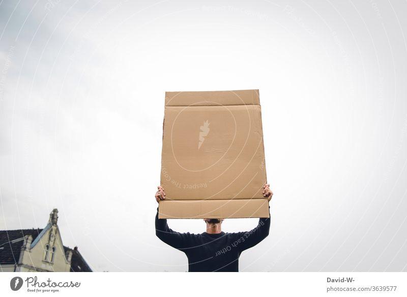 ein Mann hält ein Schild aus Pappe in die Luft und verdeckt sein Gesicht Meinungsäußerung Meinungsfreiheit aufmerksam 1 Mensch neutraler hintergrund Karton