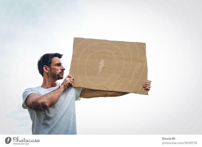 eine Person hält ein Pappschild aus Karton in den Händen, präsentiert es und schaut sich an was dort geschrieben sein könnte Meinungsäußerung Meinungsfreiheit
