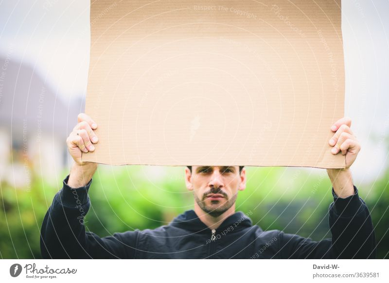 Karton aus Pappe -  Mann hält ein Schild aus Pappkarton in der Hand in die Luft pappkarton Hinweis hinweisend achtung Meinung Mannfesthalten Textfreiraum