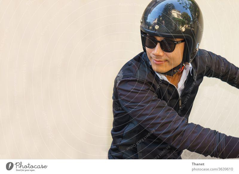 Junger asiatischer Motorradfahrer in schwarzer Jacke blickt beim Motorradfahren zurück. Biker schwarze Jacke gutaussehend Schutzhelm Mann Reiter Sonnenbrille