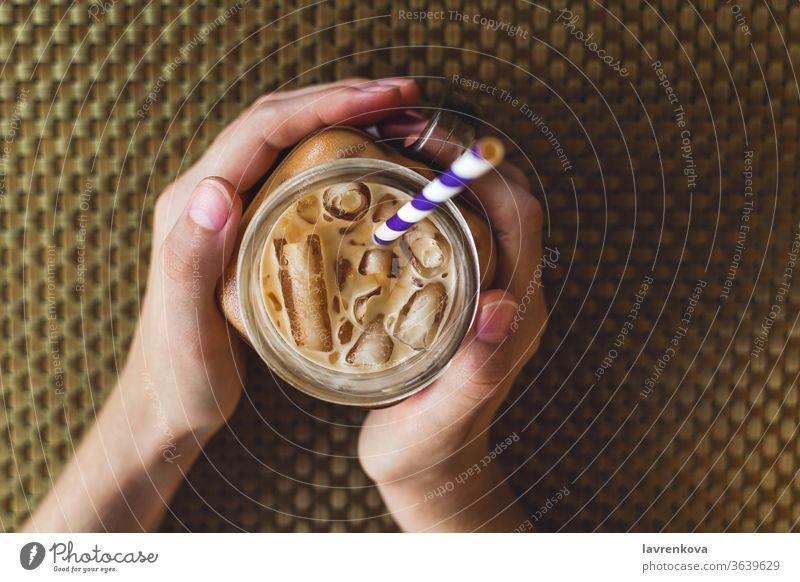 Flachlegung eines gemauerten Glases mit Eistee oder Kaffee, selektiver Fokus Getränk Koffein kalt cool trinken Frau Finger Lebensmittel Hände Gesundheit