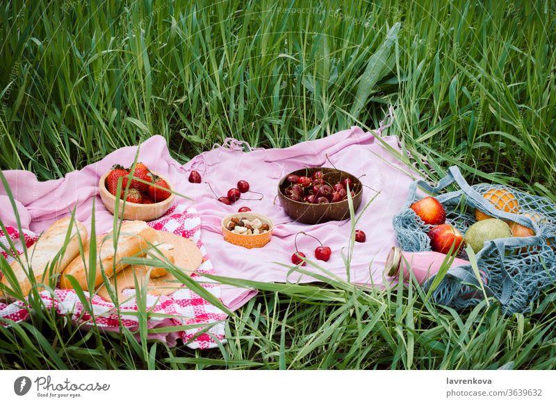 Abfallfreies Sommerpicknick mit Kirschen in den hölzernen Kokosnussschalen, frischem Brot und einer Glasflasche Saft oder Smoothie auf rosa Decke, Flatlay Äpfel