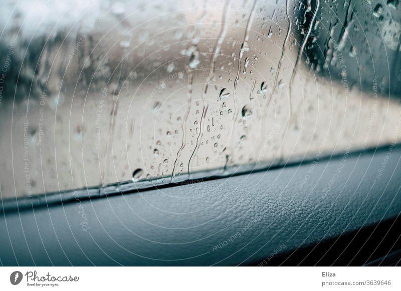 Blick aus dem Autofenster bei Regen Regentropfen Fensterscheibe schlechtes Wetter PKW Fahrzeug nass Herbst autofahren Wassertropfen Tropfen Detailaufnahme