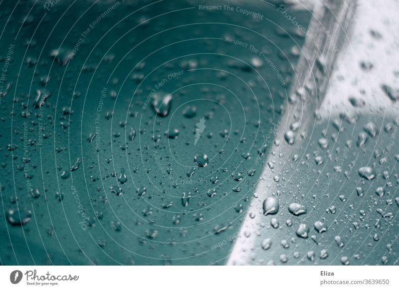 Wassertropfen nach dem Regen auf der Motorhaube eines Autos nass Lack blau Tropfen abperlen Detailaufnahme Metall Wetter Reflexion & Spiegelung PKW