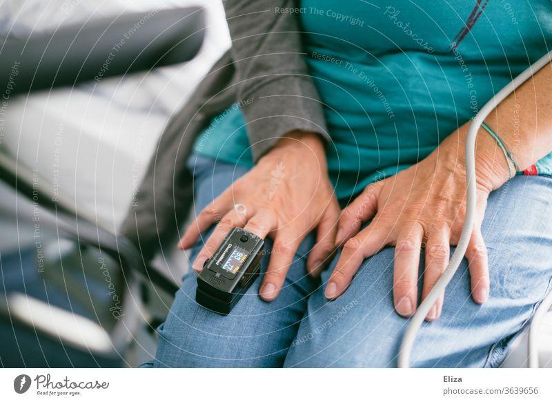 Eine Frau im Krankenhaus mit einem Pulsoximeter, zur Messung des Pulses und der Sauerstoffsättigung im Blut, am Mittelfinger pulsmessung Untersuchung