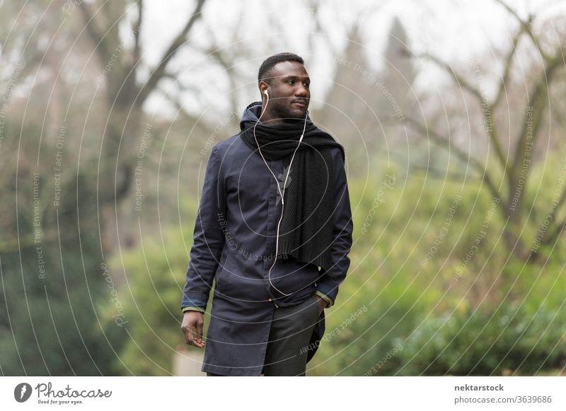 Hübscher schwarzer Mann geht im Park spazieren und hört Kopfhörer Porträt afrikanische ethnische Zugehörigkeit öffentlicher Park hören Musik Hörbuch