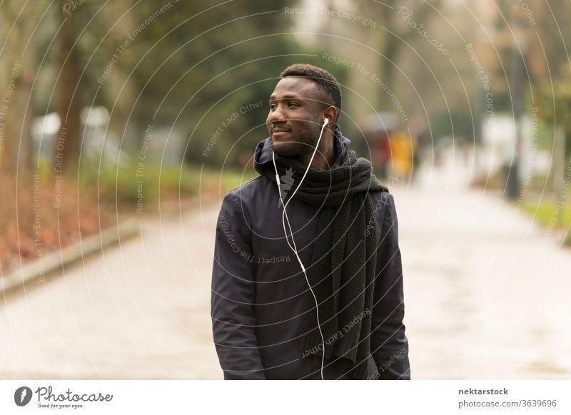 Junger schwarzer Mann mit Kopfhörern schaut weg und geht im Park spazieren Porträt afrikanische ethnische Zugehörigkeit öffentlicher Park hören Musik Hörbuch