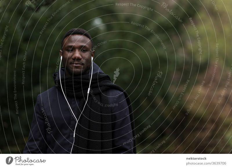 Junger Mann hört Hörbuch im Park Porträt Kopfhörer afrikanische ethnische Zugehörigkeit schwarz öffentlicher Park hören Musik Modell aus dem wirklichen Leben