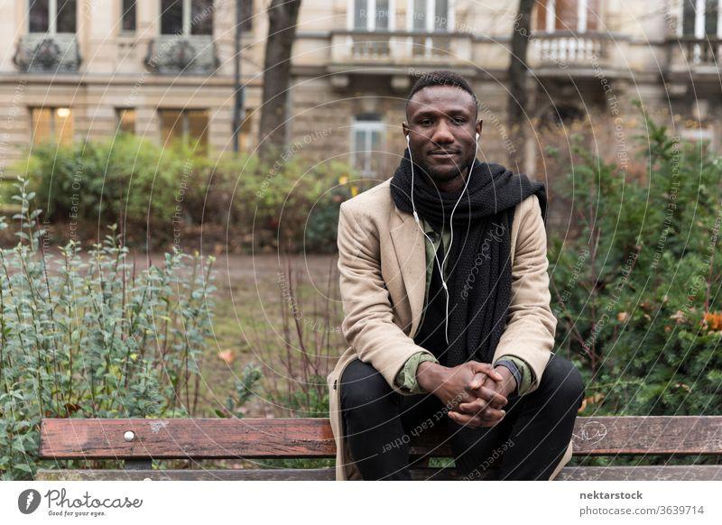Junger schwarzer Mann sitzt auf der Bank und listet ein Hörbuch auf, das in die Kamera schaut Porträt Kopfhörer afrikanische ethnische Zugehörigkeit