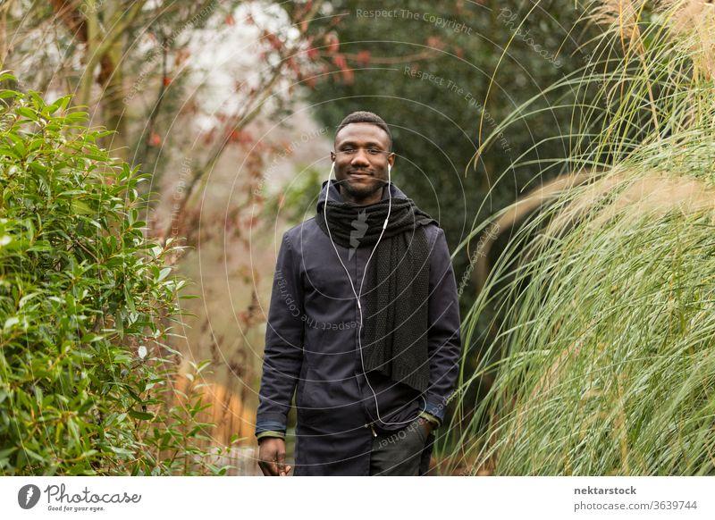 Fröhlicher schwarzer Mann mit Kopfhörern posiert im Park Porträt afrikanische ethnische Zugehörigkeit Herbstblattfarbe Gras hoch öffentlicher Park hören Musik