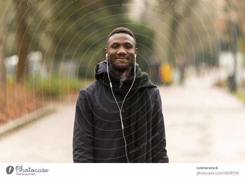 Junger Mann lauscht Kopfhörern, die selbstbewusst in die Kamera lächeln Porträt afrikanische ethnische Zugehörigkeit schwarz öffentlicher Park Straße Nachlauf