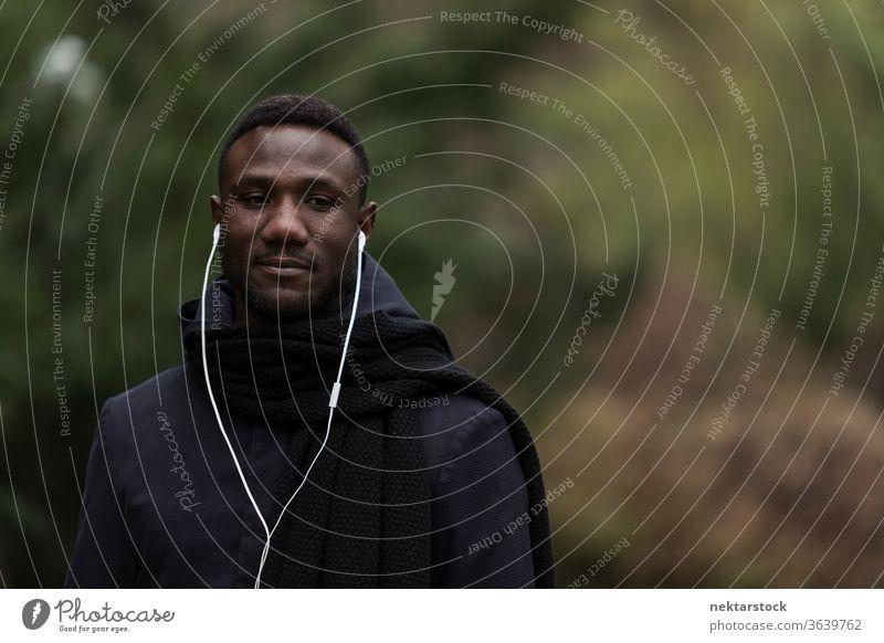 Porträt eines jungen schwarzen Mannes, der im Park Kopfhörer hört afrikanische ethnische Zugehörigkeit öffentlicher Park hören Musik Hörbuch