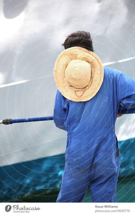 Besatzungsmitglied beim Ausbessern von Farbe auf einem Passagierkreuzfahrtschiff, das im Hafen angedockt ist. Malerei Kreuzfahrtschiff Portwein Pier Arbeiter