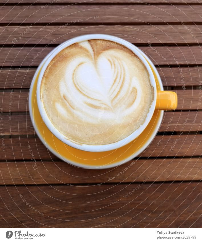 Gelbe Tasse Kaffee mit Milch auf dunklem Hintergrund. Heißer Latte oder Cappuccino mit Schaum mit Herz auf einem Holztisch mit Kopierraum. Ansicht von oben.