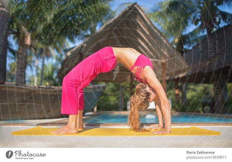 urdhva dhanurasana.foto des Mädchens beim Yoga am Pool in einem Ferienort Frau jung Pose Lifestyle Gleichgewicht Fitness Gesundheit Übung Training Menschen