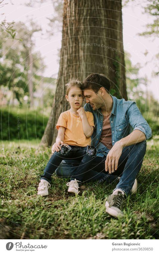 Alleinerziehender Vater sitzt mit kleiner Tochter im Gras am Baum Natur Mädchen Glück Mann Park Menschen Familie Eltern Kind Liebe Papa Spaß Erwachsener