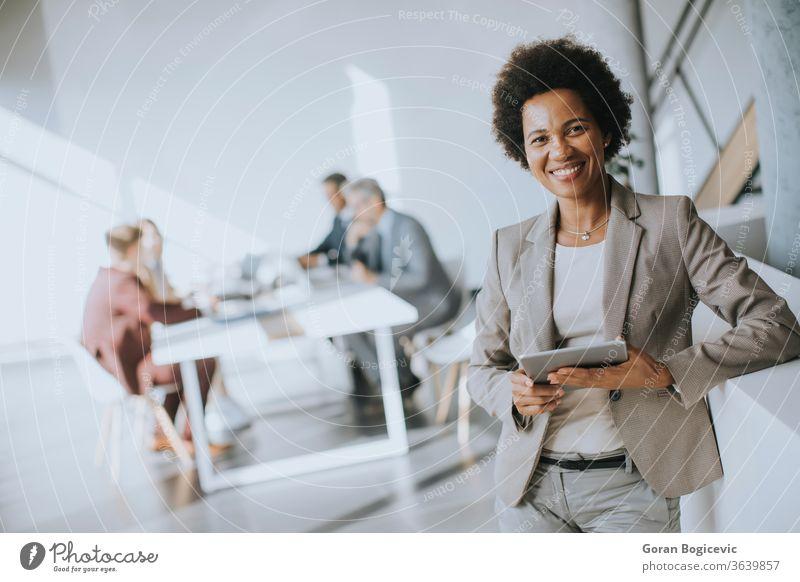 Junge afroamerikanische Geschäftsfrau steht mit digitalem Tablet in einem modernen Büro Tablette Frau Business schwarz Technik & Technologie Arbeit jung