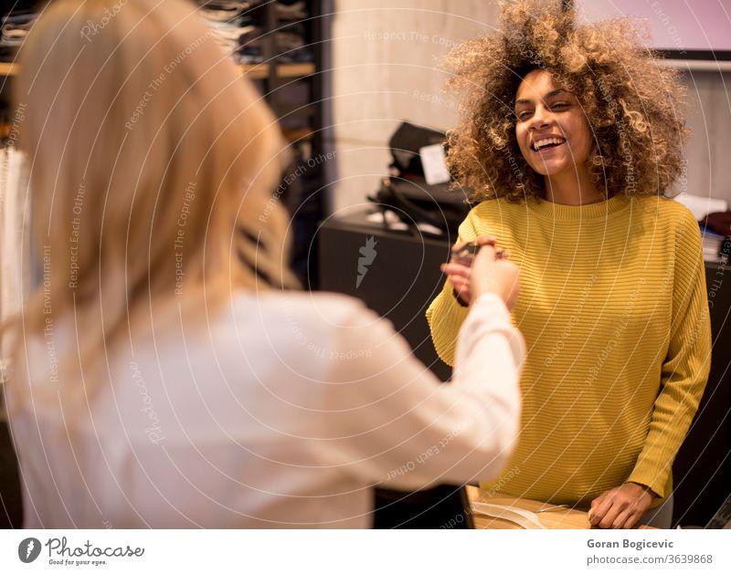Hübsche junge Frau kauft Kleidung im Modegeschäft Bekleidung Vollbart Boutique Käufer kaufen lässig Wahl auserwählend Verbraucher Konsumverhalten Kunde
