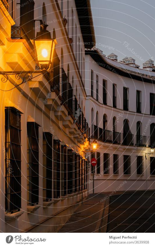 Straße mit vielen Fenstern und Balkonen an der Fassade, alle gleich und wiederholt und mit eingeschalteten Straßenlaternen Laternenpfähle Architektur Außenseite