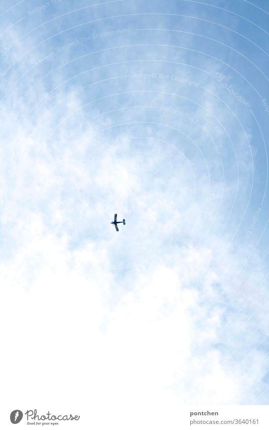 Froschperspektive- Ein kleines Flugzeug fliegt am blauen, bewölkten Himmel fliegen freiheit wolken himmel reisen fortbewegung Luftverkehr Tourismus Klimawandel
