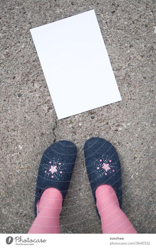 frau in hausschuhen steht vor einem auf der straße liegenden leeren weißen blatt papier, das beschriftet werden kann .. Frau stehen Hausschuhe Asphalt Straße