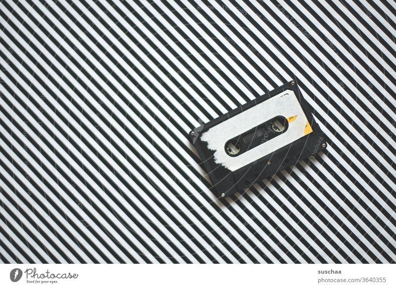 alte kasette auf gestreiftem hintergrund damals Kassette Kassettenrekorder Kompaktkassette Audiokassette Tonträger elektromagnetisch analog Aufzeichnung Musik