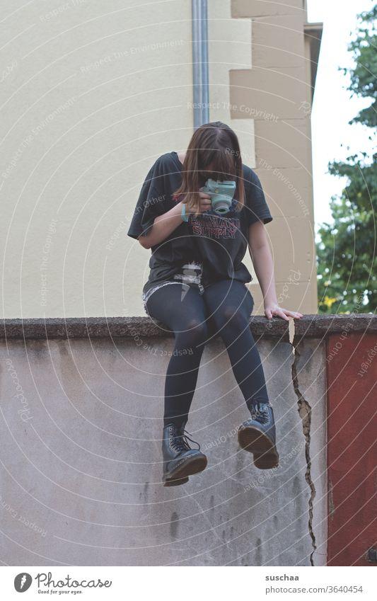 teenagerin, die auf einer mauer sitzt und ihre füße fotografiert Beine Füße Schuhe Stiefel cool sitzen Jugendliche Mauer Mauerriss Außenaufnahme Strumpfhose