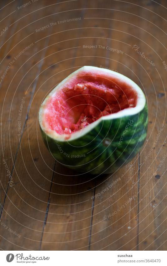 ausgehöhlte melone auf einem holzboden Melone Wassermelone Frucht gesund lecker aufgegessen Fruchtfleisch innen saftig gesunde Ernährung Durstlöscher Sommer
