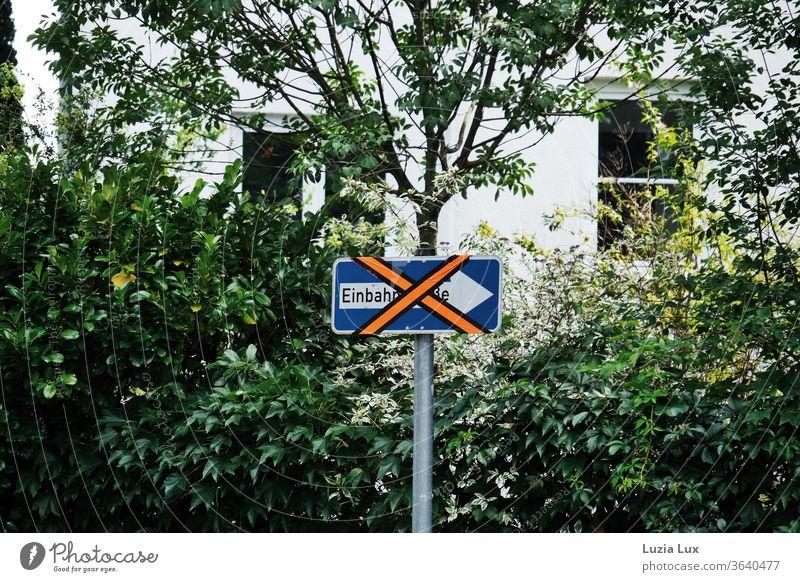 Ein etwas älteres Einbahnstraßen-Schild wird derzeit nicht benötigt und wurde deshalb leuchtend orange beklebt Strassenschild durchgestrichen skurril X