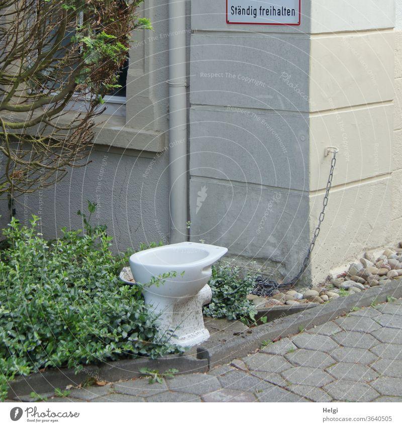 """freihalten - ausgediente Toilettenschüssel steht vor einem Haus, an der Wand ein Schild """"Ständig freihalten"""" Klo Klosett Einfahrt Vorgarten Strauch Kette"""
